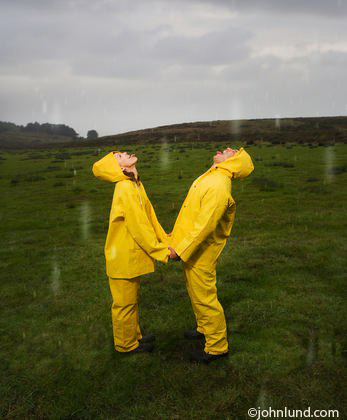 Hispanic couple in yellow wet weather rain gear with faces turned up to the sky as rain drops descend upon them. Romantic picture of a couple in rain coats standing in a rain storm on a grassy hill in the country side.
